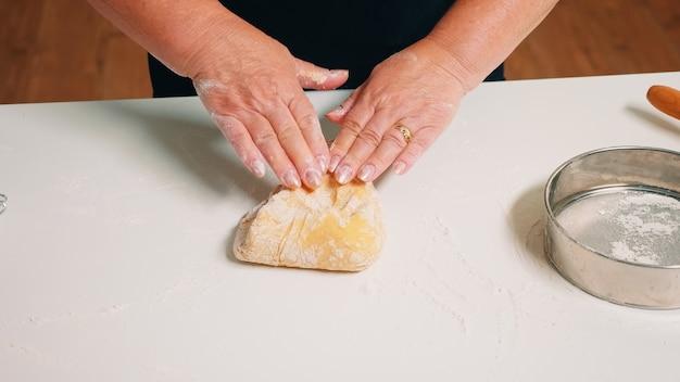 Close-up shot van handen van senior bakkerij deeg kneden. gepensioneerde oudere bakker met bonete die ingrediënten mengt met gezeefd tarwemeel dat zich vormt op een met bloem bestoven oppervlak voor het bakken van traditionele cake, brood