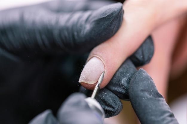 Close-up shot van hardware manicure in een schoonheidssalon. manicure past elektrische nagelvijl toe