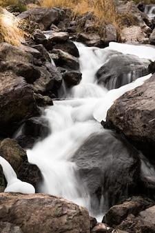 Close-up shot van het water dat door stenen stroomt
