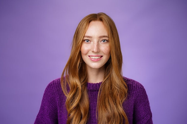 Close-up shot van hoopvolle en optimistische gelukkige jonge roodharige 20s meisje met sproeten en lang haar vrolijk lachend met vertrouwen in de ogen en prominente blik poseren tegen paarse achtergrond.