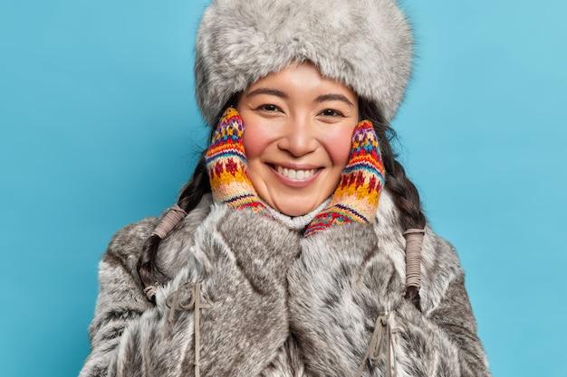 Close-up shot van inheemse vrouw houdt handen in gebreide wanten op gezicht glimlacht toothily kijkt gelukkig naar voorzijde draagt warme bont grijze jas en hoed geniet van ijzige dag geïsoleerd over blauwe muur