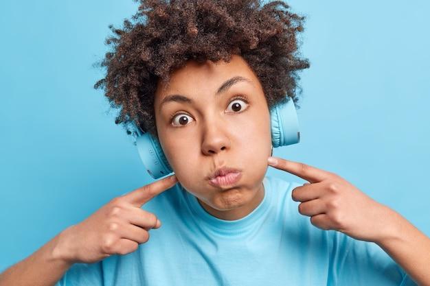 Close-up shot van jonge afro-amerikaanse vrouw pruilt wangen blaast gezicht heeft verbijsterd uitdrukking gekleed in casual kleding draagt stereo hoofdtelefoon luistert audio track geïsoleerd op blauwe muur