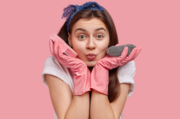 Close-up shot van jonge kamermeisje maakt grimas, houdt beide handen in de buurt van wangen, draagt dweilen, reinigt stof, toont goede hotelservice
