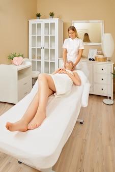 Close-up shot van jonge vrouwelijke masseur massage op het gezicht maken voor jonge mooie vrouwelijke cliënt in de spa salon