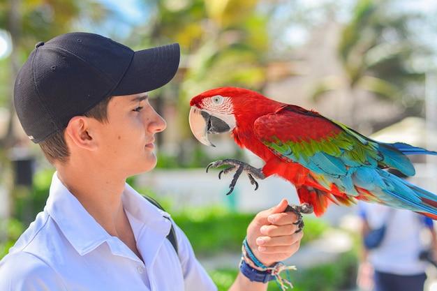 Close-up shot van jongen met papegaai in de hand