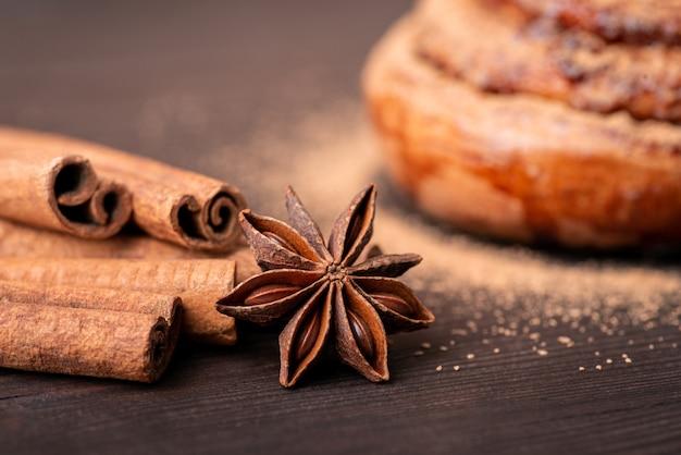 Close-up shot van kaneelstokjes en anijs ster met een broodje op de achtergrond. pittig brood koken met kaneel