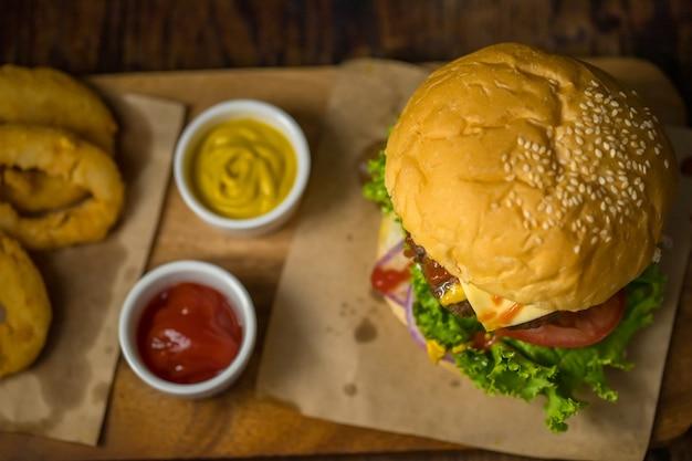 Close-up shot van klaar om zelfgemaakte rundvlees hamburger te eten met verse groenten met twee kleuren inhaalslag.