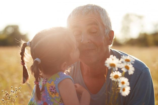 Close-up shot van kleine kleinkind omhelzen en kust haar grootvader die camomiles geeft, samen wandelen in het platteland