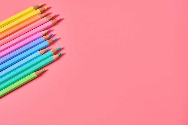 Close-up shot van kleurpotloden op een roze achtergrond met kopie ruimte