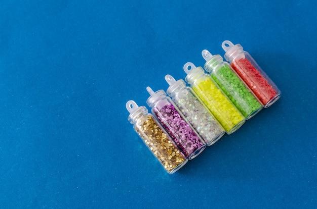 Close-up shot van kleurrijke glitter in de transparante pot op een blauwe achtergrond