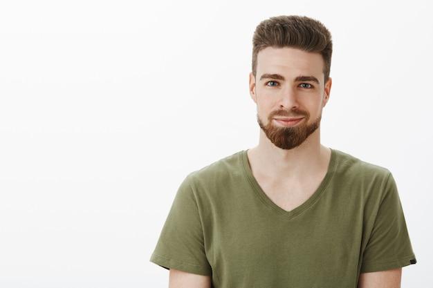 Close-up shot van knappe aardige blanke bebaarde man met blauwe ogen in v-hals t-shirt glimlachend opgetogen en geamuseerd naar je kijken met zachte blik tegen witte muur