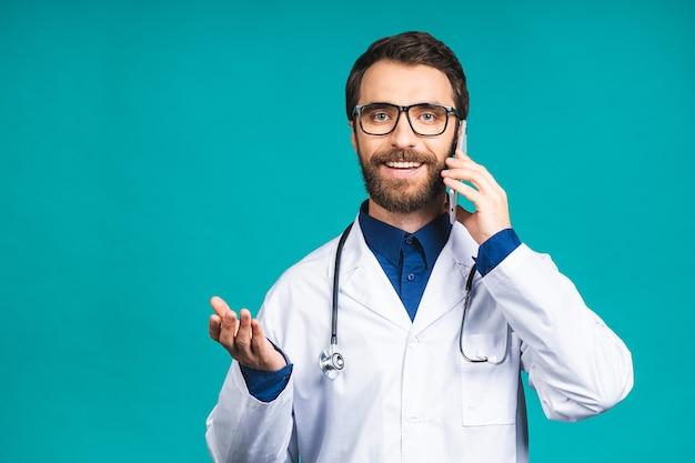 Close-up shot van knappe jonge man arts geïsoleerd op blauwe achtergrond praten op smartphone, positief glimlachend. mobiele telefoon gebruiken.