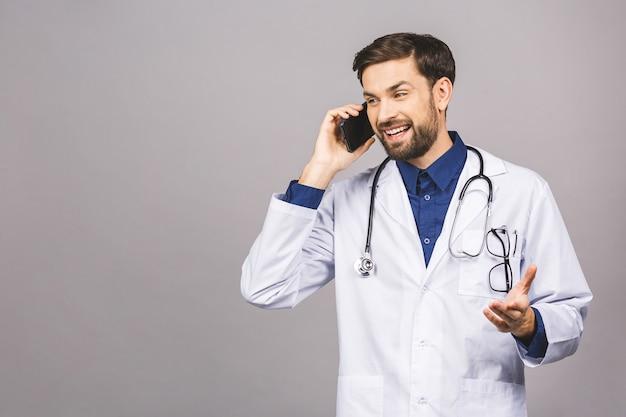 Close-up shot van knappe man arts geïsoleerd op een grijze achtergrond praten over smartphone, positief glimlachend