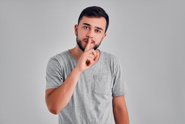 Close-up shot van knappe man met shhh gebaar, vragen om stilte of stil te zijn, geïsoleerd op een grijze achtergrond