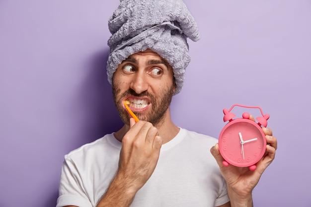 Close-up shot van knappe man met stoppels, wordt 's ochtends wakker, houdt wekker met tijd vast, poetst tanden met tandpasta, draagt een wit t-shirt en een handdoek op het hoofd