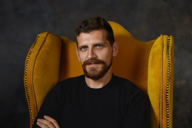 Close-up shot van knappe ongeschoren man met blauwe ogen, wazige baard en snor binnenshuis ontspannen, zittend geïsoleerd in een stijlvolle fauteuil. mensen, stijl, interieur en meubelconcept