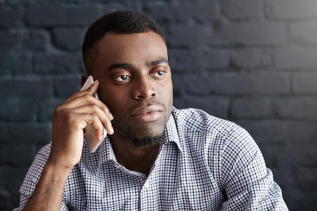 Close-up shot van knappe zakenman in formele slijtage met ernstig telefoongesprek