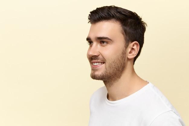 Close-up shot van knappe zelfverzekerde jonge blanke man met haren en stijlvol kapsel poseren geïsoleerd tegen lege kopie ruimte studio muur achtergrond met vrolijke, gelukkige glimlach, in goed humeur zijn