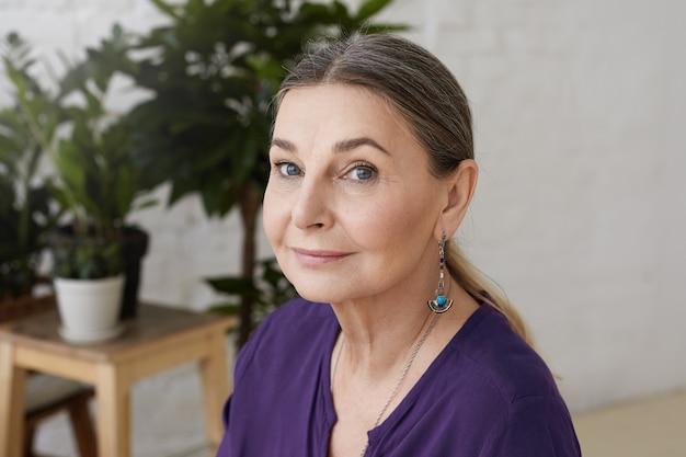 Close-up shot van lachende charmante kaukasische oudere dame met blauwe ogen, grijs verzameld haar en rimpels poseren binnenshuis
