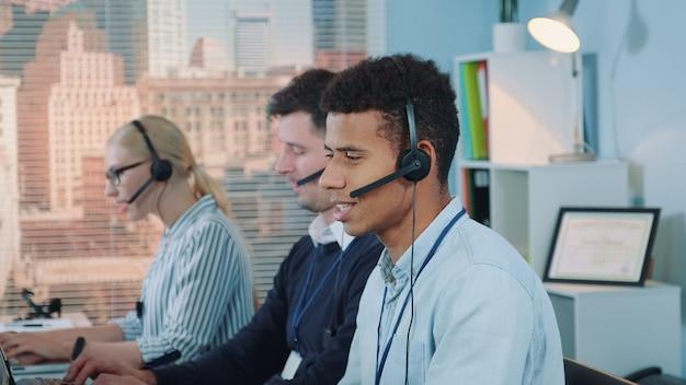 Close-up shot van lachende man van gemengd ras nemen oproep in drukke callcenter