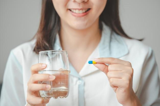 Close-up shot van lachende vrouw met capsule pil