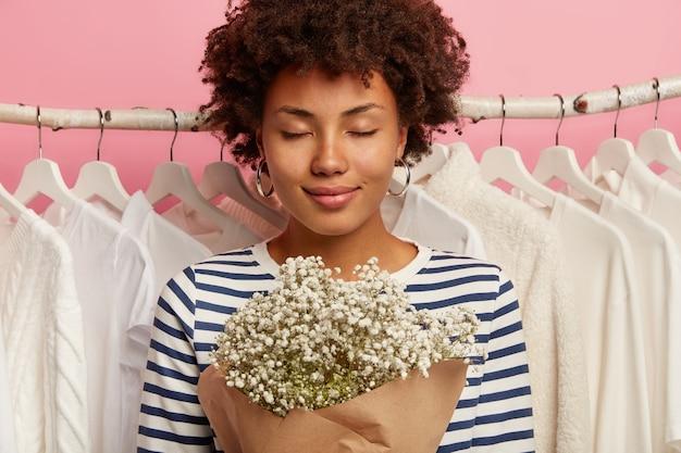 Close-up shot van leuke vrouw met afro kapsel, mooi boeket, houdt de ogen gesloten, draagt casual outfit, vormt tegen huisgarderobe