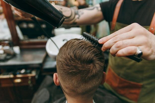 Close-up shot van man trendy kapsel krijgen bij kapperszaak. de mannelijke kapper in tatoeages die de klant bedient, haar droogt met een haardroger