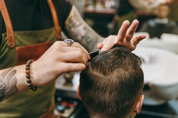 Close-up shot van man trendy kapsel krijgen bij kapperszaak. de mannelijke kapper in tatoeages ten dienste van de klant.
