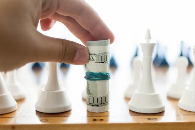 Close-up shot van mannenhand die gedraaide bankbiljetten vasthoudt en zet doet bij schaken