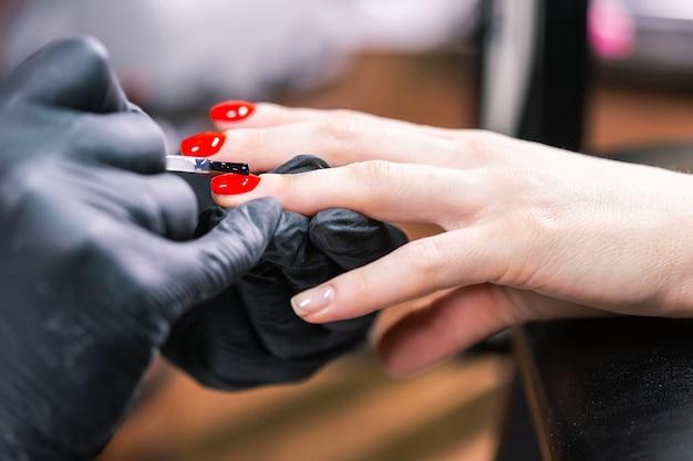Close-up shot van meester in rubberen handschoenen die betrekking hebben op rode nagels met toplaag in de schoonheidssalon