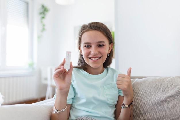 Close-up shot van meisje met een negatief testapparaat. gelukkig jong meisje toont haar negatieve coronavirus - covid-19 snelle test. coronavirus