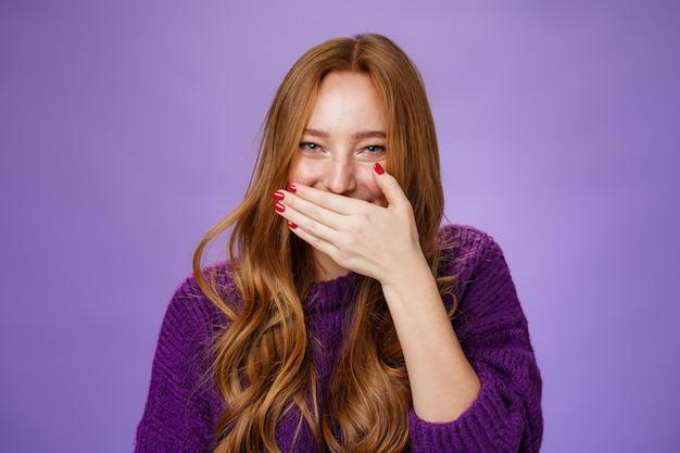 Close-up shot van meisje met plezier giechelen, mond bedekken met palm als lachend glimlachend oprecht en zorgeloos reageren op hilarische grap of grap poseren over paarse achtergrond.