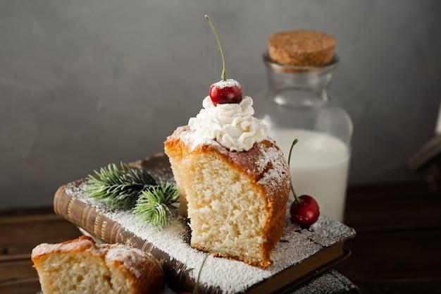 Close-up shot van melk, een heerlijke cake met room, poedersuiker en kersen op boeken