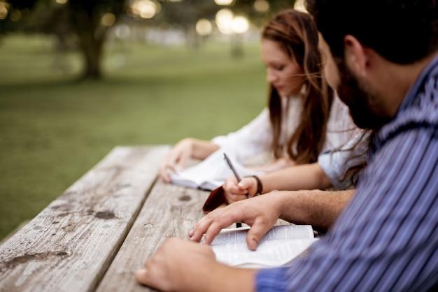 Close-up shot van mensen zitten in het park en het lezen van de bijbel