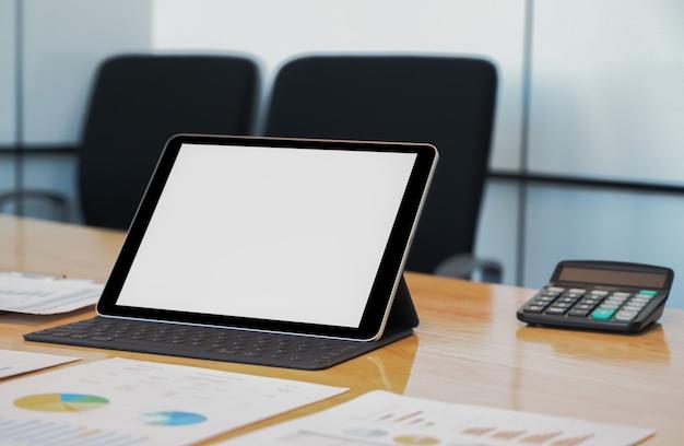 Close - up shot van mockup moderne tablet met gegevensgrafiek op het bureau.