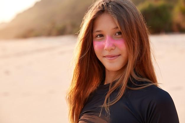 Close-up shot van mooie blanke meisje met roze surf zink masker, gekleed in zwarte wetsuit