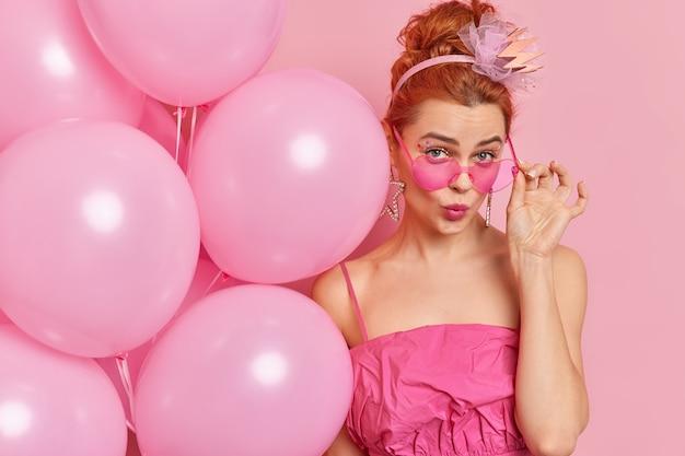 Close-up shot van mooie charmante roodharige glamour jonge vrouw kijkt onder trendy roze zonnebril gekleed in modieuze outfit houdt helium ballonnen stands binnen viert verjaardag.