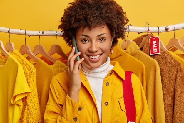 Close-up shot van mooie gekrulde vrouw belt, glimlacht breed, gekleed in gele jas