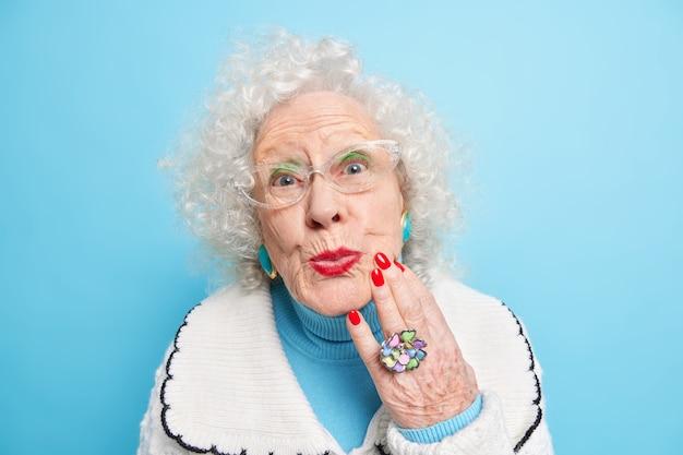 Close-up shot van mooie gerimpelde krullende volwassen vrouw onderzoekt haar huid raakt gezicht heeft rode manicure en lippen draagt sieraden stijlvolle kleding