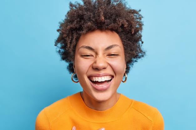 Close-up shot van mooie jonge afro-amerikaanse vrouw met natuurlijk krullend haar glimlacht in grote lijnen heeft een positieve uitstraling in een goed humeur draagt oranje trui geïsoleerd over blauwe muur