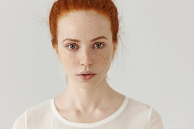 Close-up shot van mooie jonge roodharige europese vrouw met buitengewone uitstraling binnenshuis ontspannen. knap mooi meisje met gemberhaar en sproeten over haar hele gezicht poseren bij witte muur