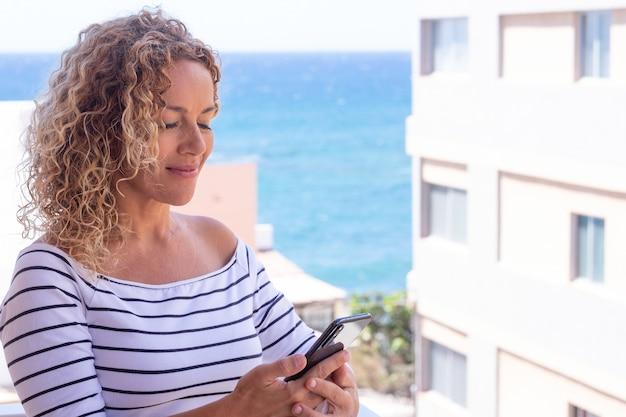 Close-up shot van mooie krullende vrouw die lacht tijdens het gebruik van de telefoon. blauwe zee op de achtergrond. vrouwelijk model met kopieerruimte