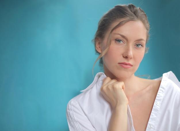 Close-up shot van mooie vrouw met wit overhemd geïsoleerd op blauw