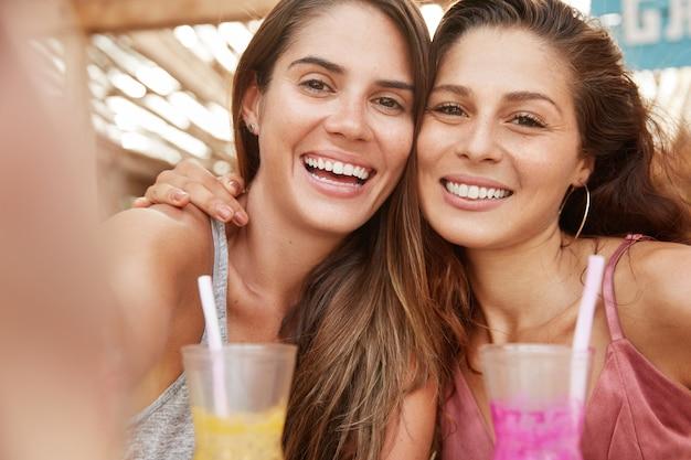 Close-up shot van mooie vrouwelijke zussen omhelzen en glimlachen vreugdevol, maak een selfie-foto wanneer ze vrije tijd doorbrengen in de cafetaria
