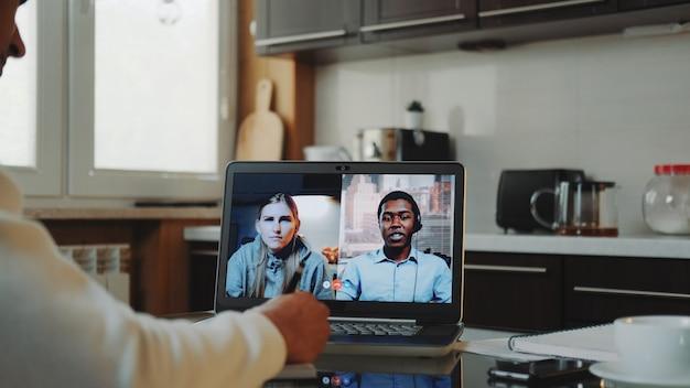 Close-up shot van multiraciale collega's die thuis aan quarantaine werken door via de computer een gemeenschappelijk videogesprek te voeren