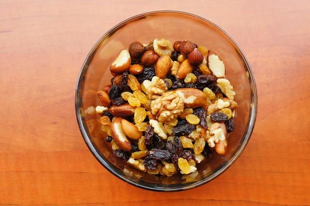 Close-up shot van noten en rozijnen mix in een kom op een houten oppervlak