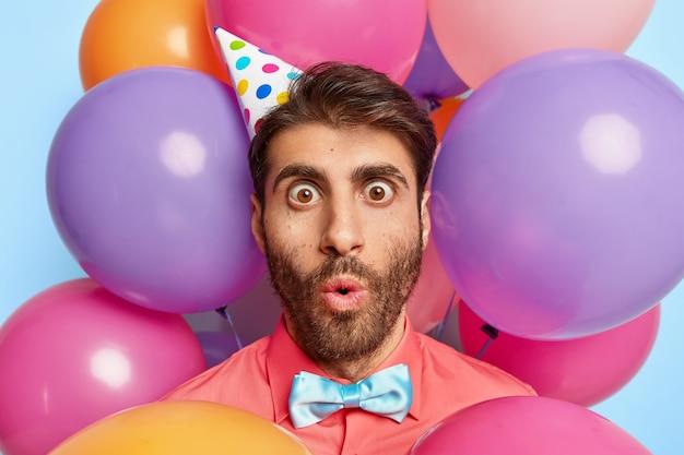 Close-up shot van onder de indruk verjaardag man staart met afgeluisterde ogen, heeft een ongelooflijke gezichtsuitdrukking, draagt een papieren kegelhoed, een elegant roze shirt en een vlinderdas
