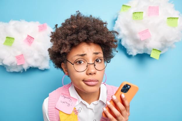 Close-up shot van ontevreden afro-amerikaanse student afgestudeerden van de universiteit bereidt zich voor op eindexamens schrijft taken op die niet te vergeten op kleurrijke stickers zoekt informatie via mobiele telefoon