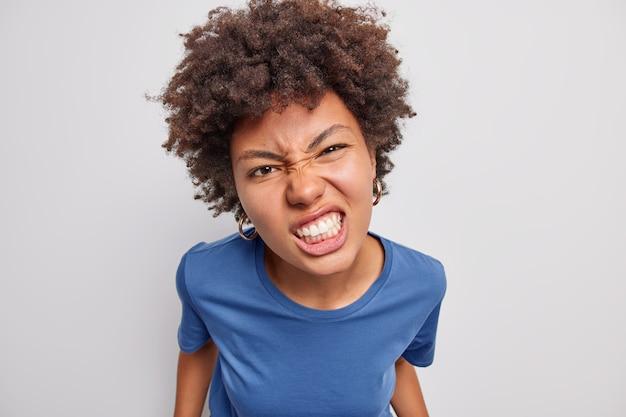 Close-up shot van ontevreden afro-amerikaanse vrouw fronst gezicht balt tanden van woede gekleed in casual blauw t-shirt drukt negatieve emoties uit tegen een witte achtergrond. woede concept