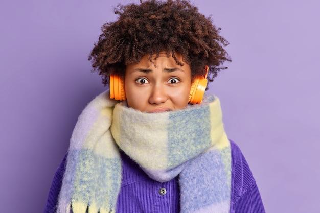 Close-up shot van ontevreden afro-amerikaanse vrouwelijke rillingen van koude draagt warme sjaal om nek besteedt veel tijd buiten in de winter luistert naar audiotrack via koptelefoon.